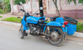 Old bright blue motorcycle with side car parked in Cuban street. Stock Photo