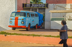 Old and bright van in Mexican town. Funny multi-colored van and a woman on the street Stock Image
