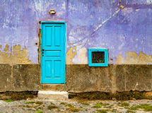 Old, bright violet wall with a blue door and window. A front view of a house with old, violet wall with peeling paint and turquioise blue door and tiny window Stock Images
