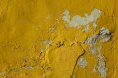 Old bright yellow shabby wall with deep relief, damage and white spots with shadows. rough surface texture. A old bright yellow shabby wall with deep relief royalty free stock photography