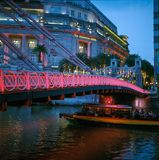 Old brightly illuminated bridge on the Singapore river and the Fullerton Hotel at sunset shot with analogue film photography stock photos