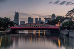 Old brightly illuminated bridge on the Singapore river at sunris Stock Image