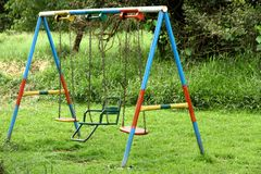 Old Brightly Painted Metal Swing Set. An old and colorful swing set in a playground in Africa royalty free stock photos