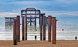 A view along the rusting pillars of The Old Brighton Pier on a bright calm day. Royalty Free Stock Image
