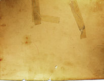 Old brittle paper with tape. Photograph of old torn brittle cracked brown vintage paper with aged tape stock photo