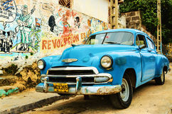 Old broken American blue car parked in the old town of Havana, Cuba. Turquoise blue and white facade of old colonial building in Trinidad, where colonial style Stock Image