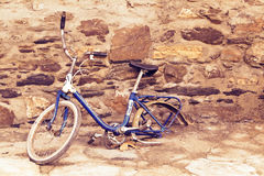 Old Broken Bike. Old broken blue bicycle without the rear wheel, leaning against a stone wall. With vintage colors Royalty Free Stock Photo