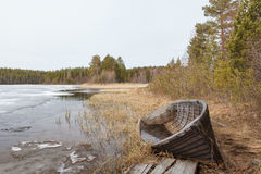 Old broken boat on the coast of river on a cloudy day. Spring, Karelia Stock Photography