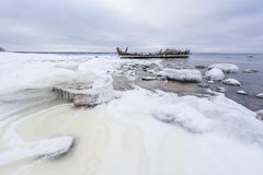 Old broken boat wreck and rocky beach in wintertime. Frozen sea, evening light and icy weather on shore like fairy tale country royalty free stock images
