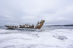 Old broken boat wreck and rocky beach in wintertime. Frozen sea, evening light and icy weather on shore like fairy tale country royalty free stock photo