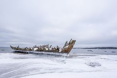 Old broken boat wreck and rocky beach in wintertime. Frozen sea, evening light and icy weather on shore like fairy tale country royalty free stock photos