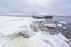 Old broken boat wreck and rocky beach in wintertime. Frozen sea, evening light and icy weather on shore like fairy tale country stock image