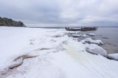 Old broken boat wreck and rocky beach in wintertime. Frozen sea, evening light and icy weather on shore like fairy tale country stock photo
