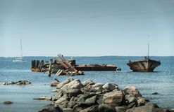 Old broken boat wreck on the shore, blue sea and sailboat on background. Harilaid, small island in Estonia, Europe Stock Photos