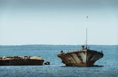 Old broken boat wreck on the shore, blue sea and sailboat on background. Harilaid, small island in Estonia, Europe Stock Photo