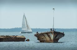 Old broken boat wreck on the shore, blue sea and sailboat on background. Harilaid, small island in Estonia, Europe Royalty Free Stock Photography