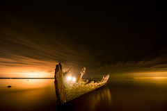 Old broken boat wreck on the shore, a frozen sea and beautiful blue sunset background. Stock Photos