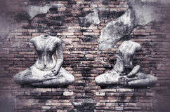 Old broken Buddha statue on grunge brick wall background with vi Royalty Free Stock Photo