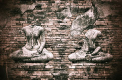 Old broken Buddha statue on grunge brick wall background with vi Stock Photography