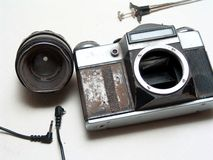 Old broken camera. Old broken rusted camera with some equipments like cable release lens and wire Royalty Free Stock Image
