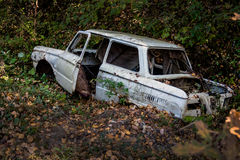 Old broken car in a forest ravine lies Stock Photography