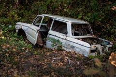 Old broken car in a forest ravine lies. Broken car in a forest ravine lies polluting nature Stock Photography