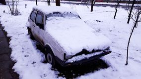 An Old White Broken Car Covered with Snow royalty free stock photography
