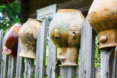 Old broken clay jugs on wooden fence stock photo