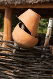 Old broken clay pot close up at wattle fence. Rural scene. Stock Photography