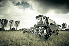 Old broken combine harvester abandoned in the field during work. Royalty Free Stock Photos