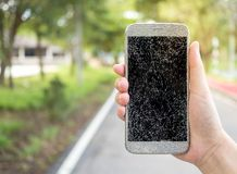 Old broken and cracked screen smartphone. Close-up image of human hand holding old broken and cracked screen smartphone on street background with copy space royalty free stock photo