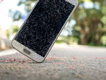 Old broken and cracked screen smartphone. Close-up image of old broken and cracked screen smartphone drop down on the floor with copy space royalty free stock photo