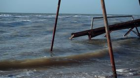 Old, broken, destroyed pavilions, awnings, flooded with water on the beach. Small waves of the muddy sea, poured roof stock video