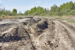 Old broken dirt road with rubbish and wood. Holes and grooves. Stock Photo