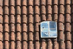 Old broken dormer window in the red tiled roof Royalty Free Stock Photography