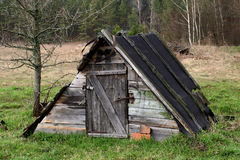 Old broken- down house in a glade Royalty Free Stock Photo