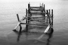 Old Broken Down Pier. A black and white image of an old deserted broken down pier stock photos