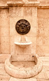 Old broken drinking fountain in the Spanish city. Tinted Stock Image