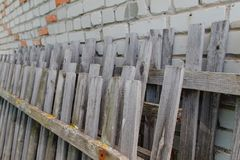 Old broken fence. The old fence has fallen off the brick wall Stock Photography