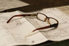 Old broken glasses on old and dirty blue prints for industrial manufacturing Royalty Free Stock Image