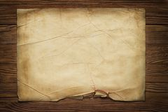 Old broken horizontal sheet of paper on brown wooden board. Piece of old paper on wood texture background stock photo
