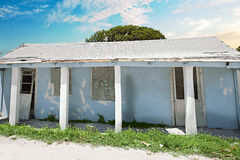 Old and broken house  with trees under the blue sky. There are concrete pillars holding the roof. some broken windows and doors with grass on the floor Royalty Free Stock Photos
