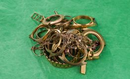 Old and broken jewelry, watches of gold on a green. A scrap of gold. Old and broken jewelry, watches of gold and gold-plated on a green background Stock Photos