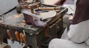Shoe in the shop of shoemaker. Old broken leather shoe in the shoemaker`s shop Stock Image