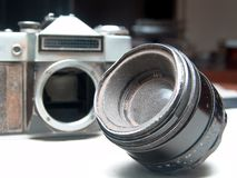 Old broken lens. Old broken rusted camera with lens in focus and the body at the back Stock Photo