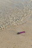 An old and broken lighter polluting the beach Stock Images