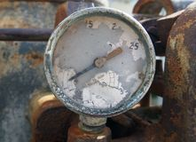 Old broken meter on an old rusty abandoned industrial engine. An old broken round meter on an old rusty abandoned industrial engine Royalty Free Stock Photo