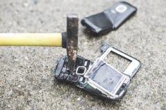 Old broken mobile phone. Hammer crease phone royalty free stock photo