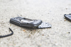 Old broken mobile phone. On the road stock image