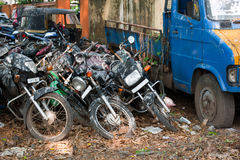 Old broken motorbikes and car in junkyard. India Royalty Free Stock Photography